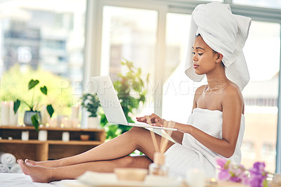 Buy stock photo Shot of an attractive young woman sitting on a massage table and using a laptop at a spa