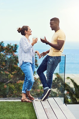 Buy stock photo Full length shot of a young couple enjoying drinks together while relaxing outdoors on holiday