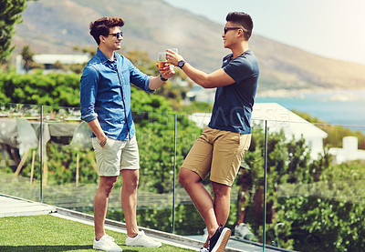 Buy stock photo Full length shot of two handsome young men having drinks and relaxing outdoors while on holiday