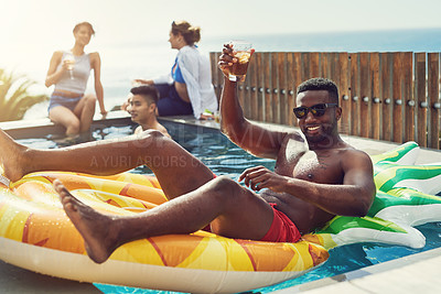 Buy stock photo Portrait of handsome young man raising up his glass for a toast while relaxing in a pool outdoors with friends