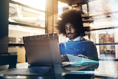 Buy stock photo Shot of a handsome young businessman using a laptop in his office at work