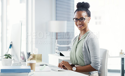 Buy stock photo Portrait of an attractive young businesswoman working at her desk in a modern office