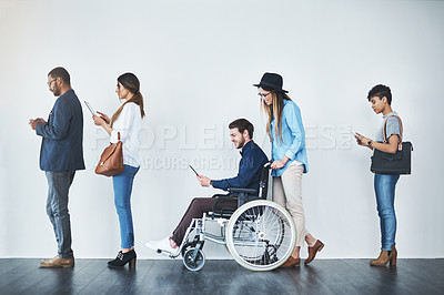 Buy stock photo Full length shot of a group of businesspeople using wireless technology while waiting in line