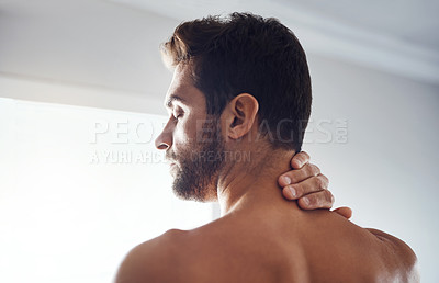 Buy stock photo Rearview shot of a handsome young man holding his neck in pain while relaxing at home