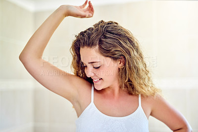 Buy stock photo Shot of an attractive young woman smelling her armpit in the bathroom at home