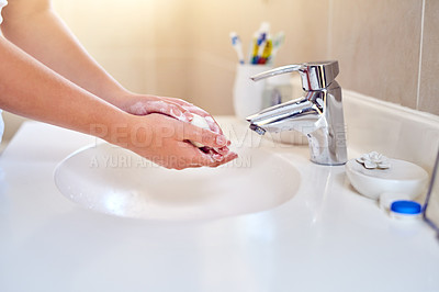Buy stock photo Closeup shot of a woman washing her hands in the bathroom at home