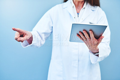Buy stock photo Closeup shot of a scientist using a digital tablet while connecting to a user interface against a blue background