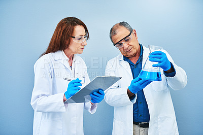 Buy stock photo Studio shot of two scientists conducting an experiment against a blue background