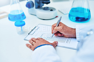 Buy stock photo Closeup shot of a scientist writing notes while working in a laboratory