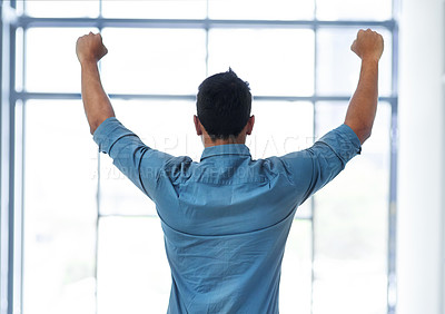 Buy stock photo Rearview shot of a young businessman with his fists raised in celebration in the office