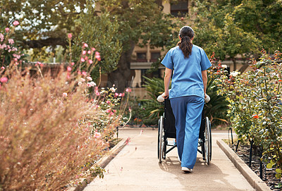 Buy stock photo Rearview shot of a caregiver pushing around a patient in a wheelchair