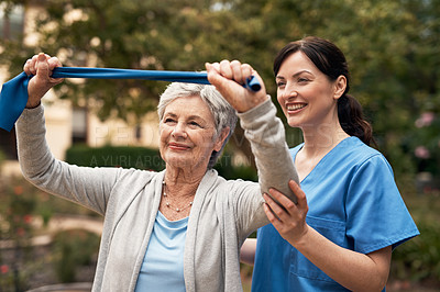 Buy stock photo Shot of a caregiver helping a senior patient with resistance band exercises