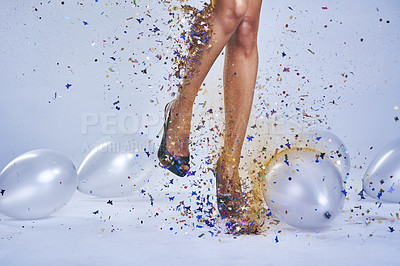Buy stock photo Studio shot of a young woman's legs in a pair of heels with confetti and balloons falling around