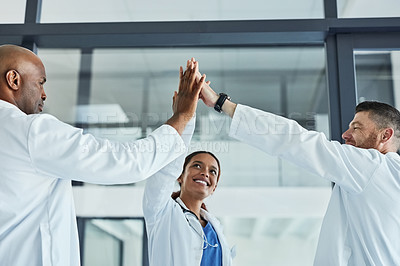 Buy stock photo Low angle shot of a group of medical practitioners giving each other a high five