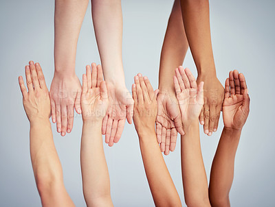 Buy stock photo Cropped studio shot of a group of women stacking their hands against a gray background