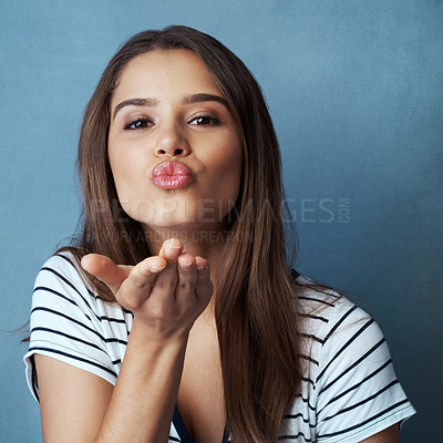 Buy stock photo Studio shot of an attractive young woman blowing a kiss against a blue background