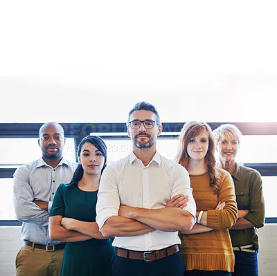 Buy stock photo Cropped portrait of a team of colleagues standing together with their arms crossed in a modern office
