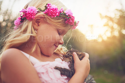 Buy stock photo Shot of a little girl holding a kitten and petting it while standing outside in nature