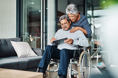 Buy stock photo Cropped shot of a cheerful elderly woman pushing her husband around in a wheelchair while he browses on a digital tablet at home during the day