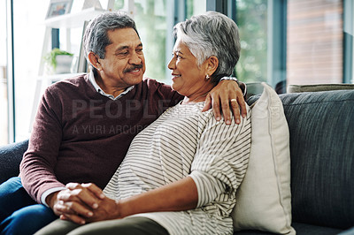 Buy stock photo Shot of a cheerful elderly couple holding hands while being seated on a couch at home