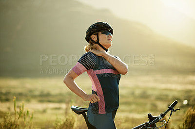 Buy stock photo Shot of a sporty woman experiencing shoulder pain while out cycling