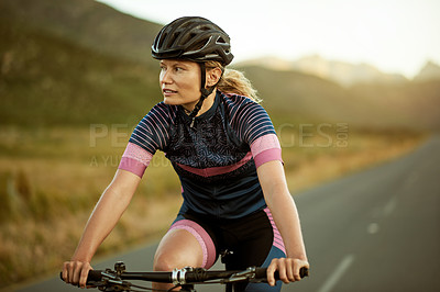 Buy stock photo Shot of a sporty young woman out cycling on a country road