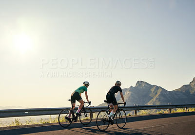 Buy stock photo Shot of two sporty young women out cycling on a country road