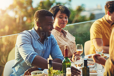 Buy stock photo Shot of cheerful young man  sitting around a table with friends at a gathering outdoors