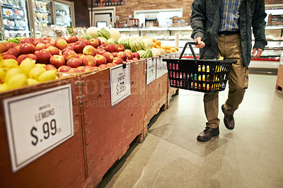 Buy stock photo Cropped shot of a man holding a basket while shopping at a grocery store