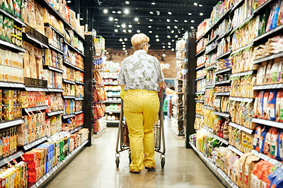Buy stock photo Rearview shot of a mature woman shopping in a grocery store