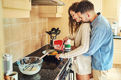 Buy stock photo Shot of a young couple working in the kitchen together