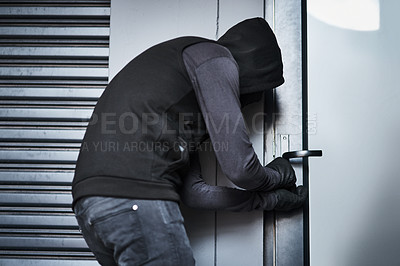 Buy stock photo Rearview shot of a male burglar busy picking the lock of a door in a garage