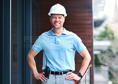 Buy stock photo Portrait of a cheerful engineer posing with his hands on his hips outside a building