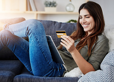 Buy stock photo Shot of a young doing online shopping while relaxing on her couch at home