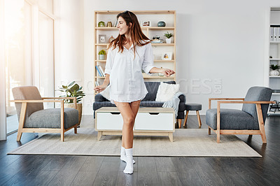 Buy stock photo Shot of a happy young woman dancing in her living room