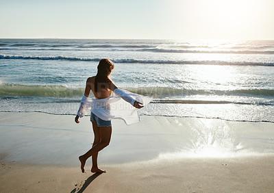 Buy stock photo Shot of a beautiful young woman enjoying herself at the beach at sunset