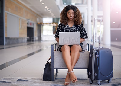 Buy stock photo Shot of a young businesswoman using a laptop in an airport