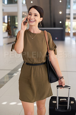 Buy stock photo Cropped shot of an attractive young businesswoman making a phonecall while walking through an airport terminal