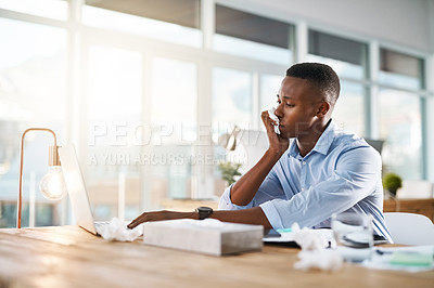 Buy stock photo Shot of a young businessman suffering with a cold while sitting at his desk at work