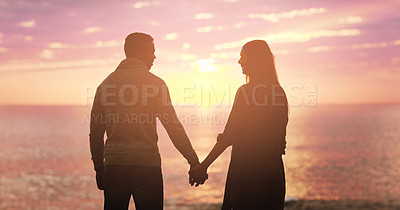 Buy stock photo Rearview shot of a happy young couple holding hands at sunset on the beach