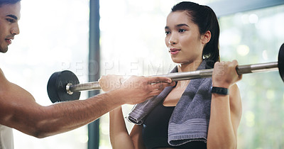 Buy stock photo Cropped shot of a young woman lifting weights with her personal trainer assisting her