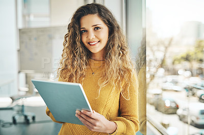 Buy stock photo Cropped portrait of an attractive young female designer using her tablet while standing in the office