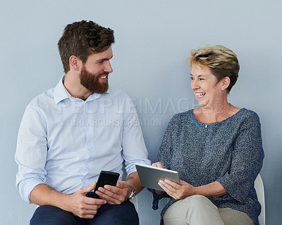Buy stock photo Studio shot of a two cheerful business people talking to each other and holding digital devices while being seated against a grey background