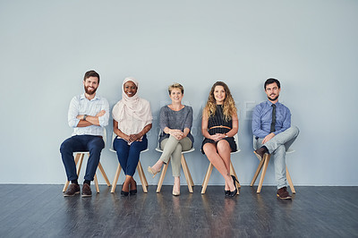 Buy stock photo Portrait of a group of cheerful businesspeople seated next to each other against a grey background