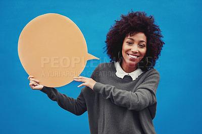 Buy stock photo Cropped shot of an attractive young woman holding a speech bubble against a blue background