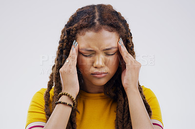 Buy stock photo Shot of a young woman holding her head while suffering from a headache against a grey background