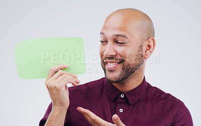 Buy stock photo Shot of a handsome young man holding a speech bubble against a grey background