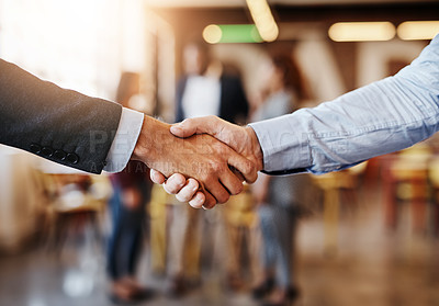 Buy stock photo Cropped shot of two unrecognizable businessmen shaking hands while standing in the office with their colleagues
