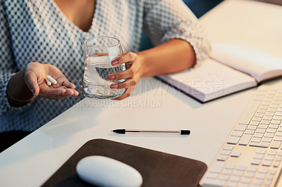 Buy stock photo Shot of an unrecognizable businesswoman taking medication in an office at night