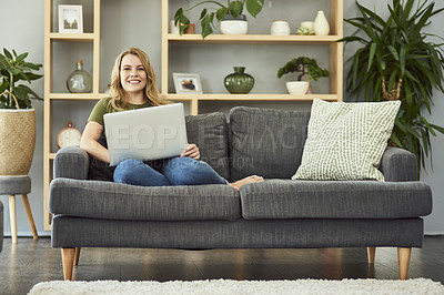 Buy stock photo Full length portrait of an attractive young woman using her laptop while relaxing on the sofa at home